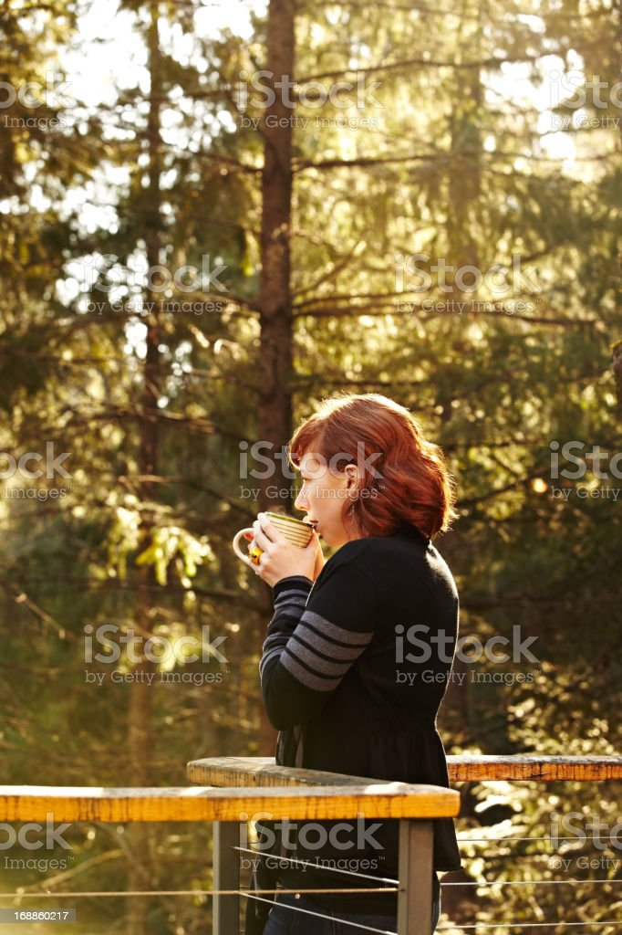 Woman drinking tea on deck in nature royalty-free stock photo