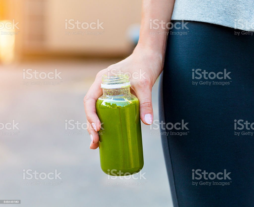 Woman drinking vegetable smoothie after fitness running workout stock photo