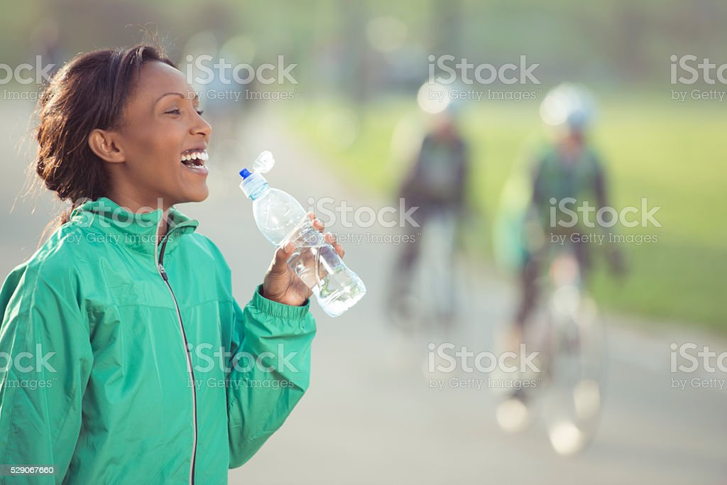 Woman drinking water after running. stock photo