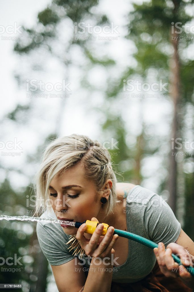 Woman drinking water from hose stock photo