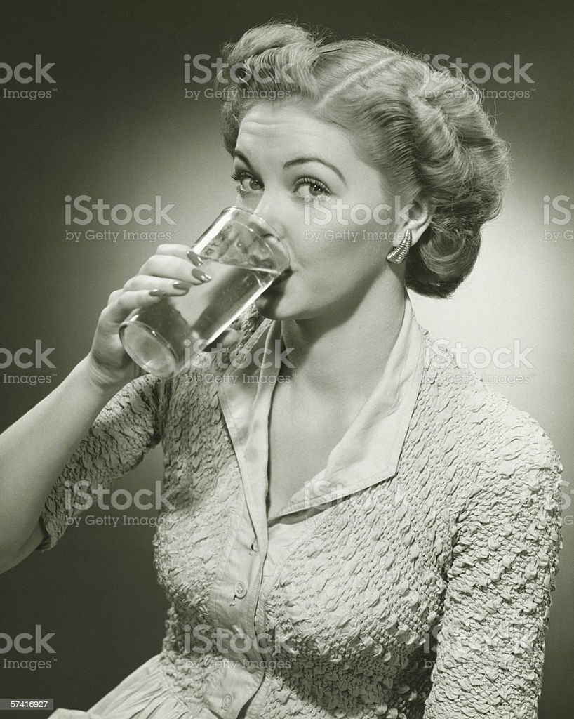 Woman drinking water from tall glass, (B&W), (Close-up), (Portrait) stock photo