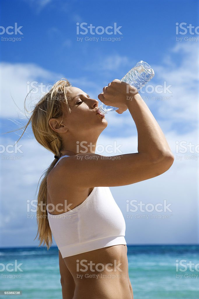 Woman drinking water on beach. royalty-free stock photo
