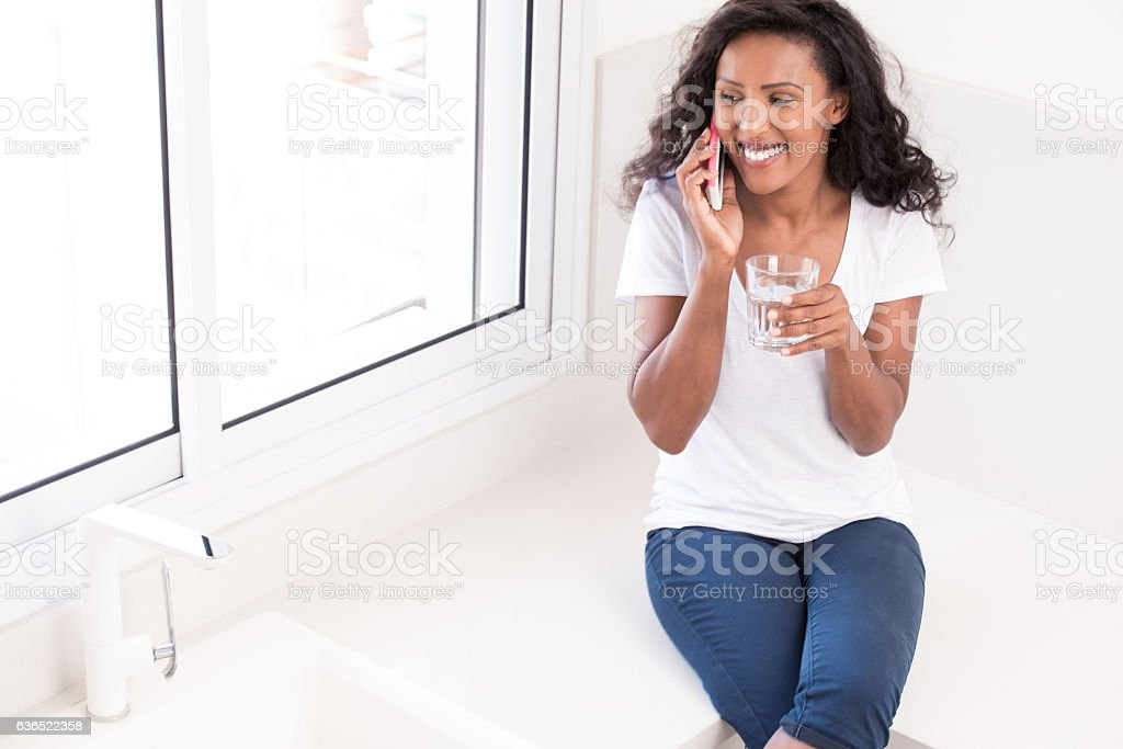 Woman drinking water while talking on smartphone. stock photo