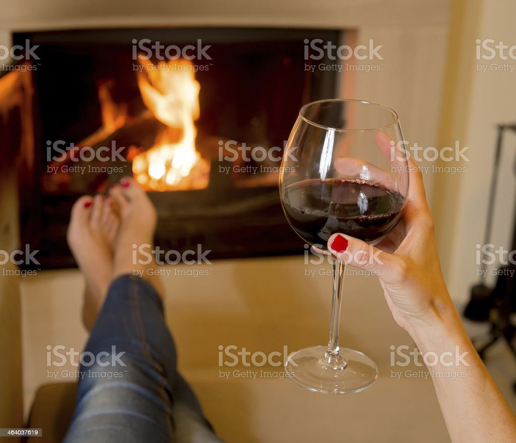 woman drinking wine in front of fire stock photo