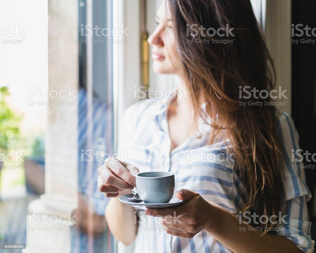 Woman drinks coffee at home stock photo