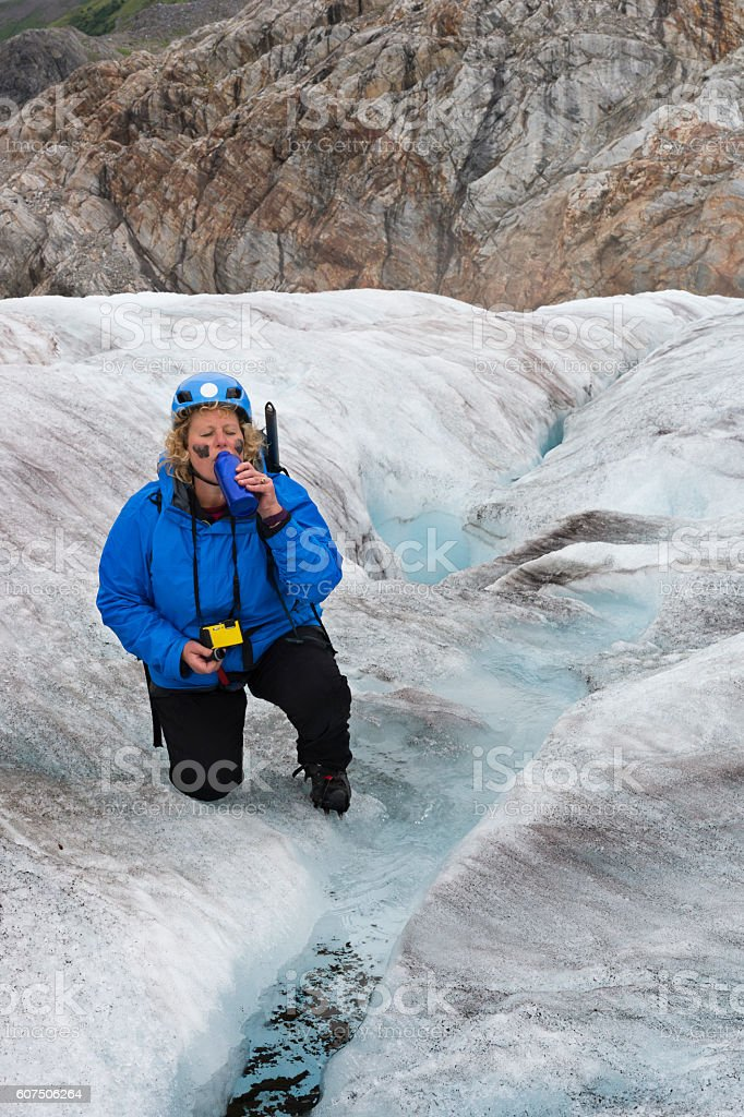 Woman drinks glacial water from stream in ice stock photo