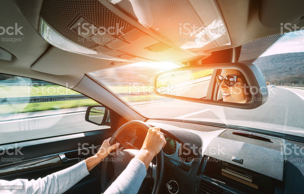Woman drive a car reflects in back view mirror stock photo