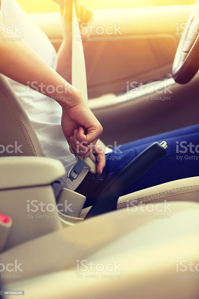 woman driver buckle up the seat belt before driving car stock photo