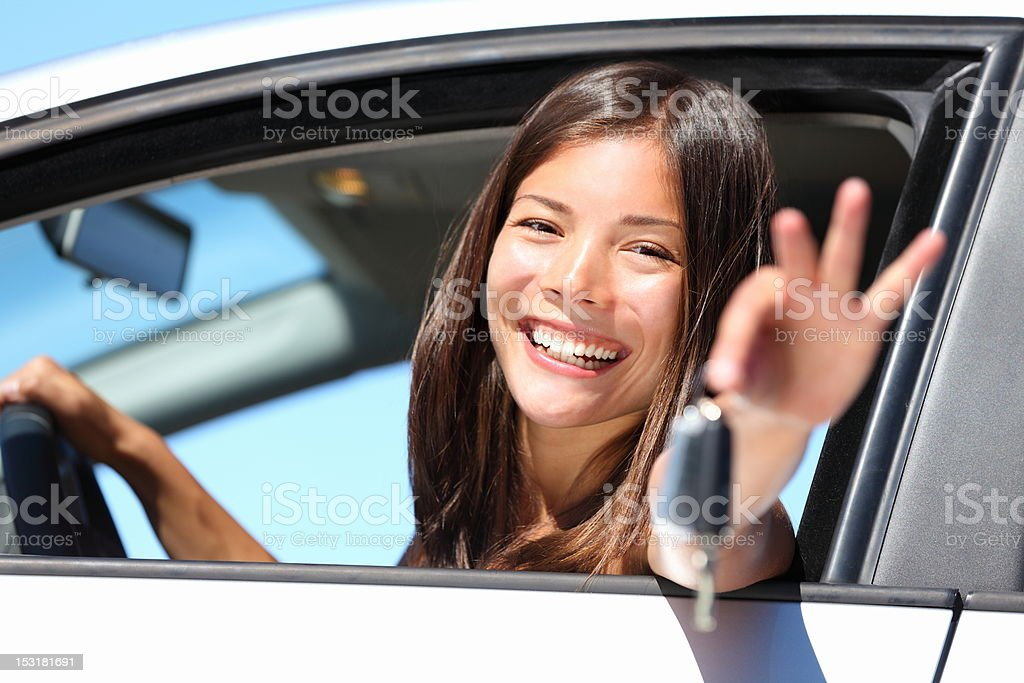 Woman driver in car showing keys stock photo