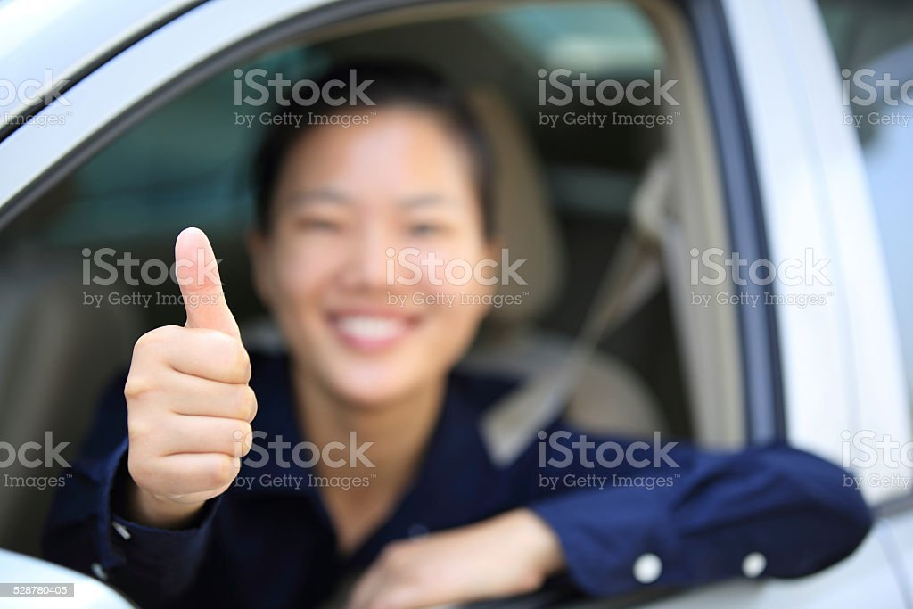 woman driver thumb up in car stock photo