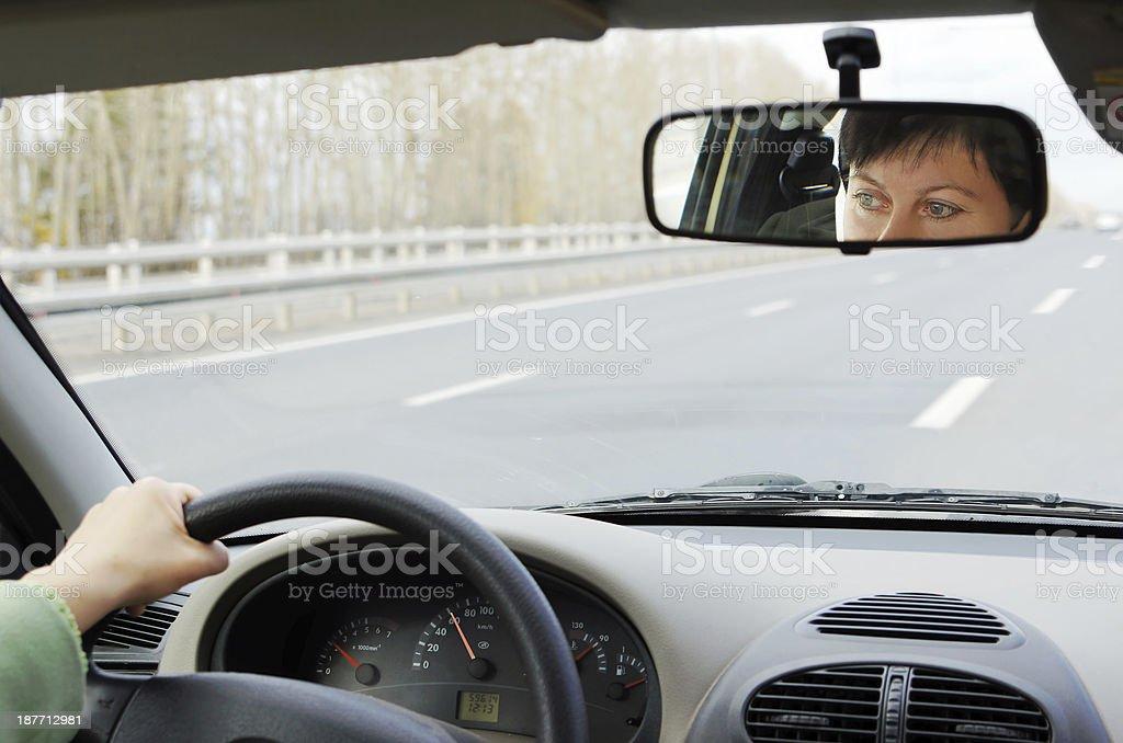 Woman drives a car along highway royalty-free stock photo
