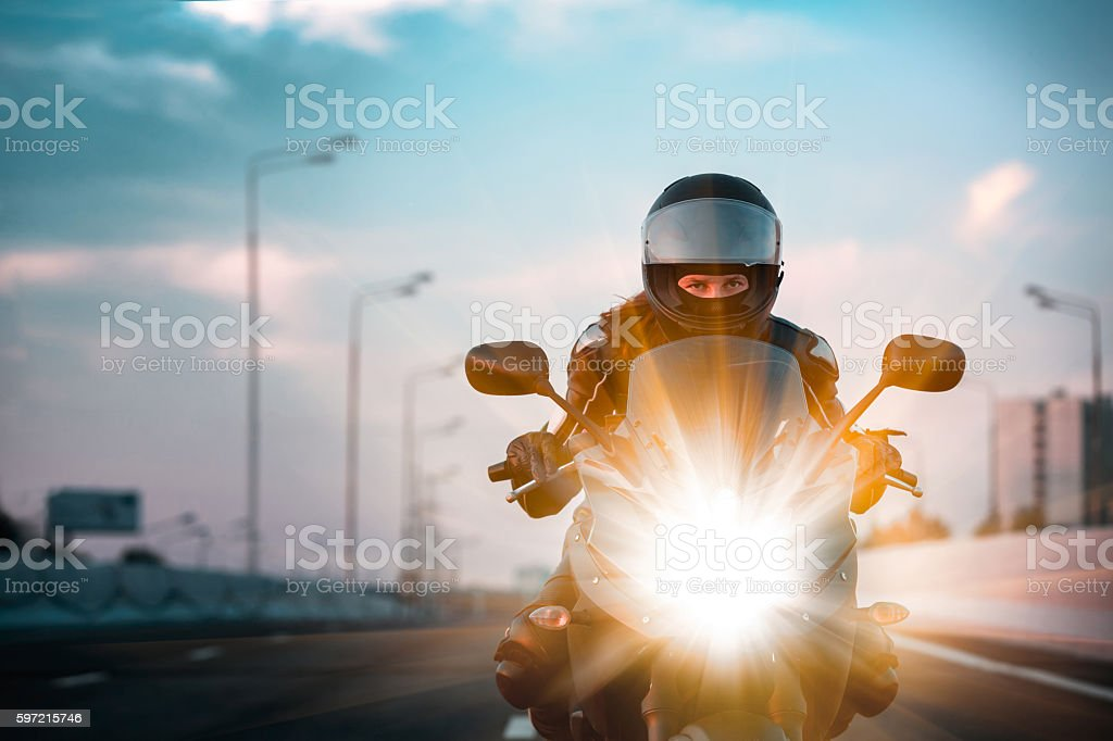 Woman drives on a motorcycle on a morning highway stock photo