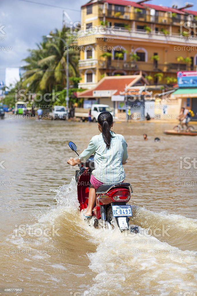 Woman drives through floodwaters in Siem Reap, Cambodia royalty-free stock photo
