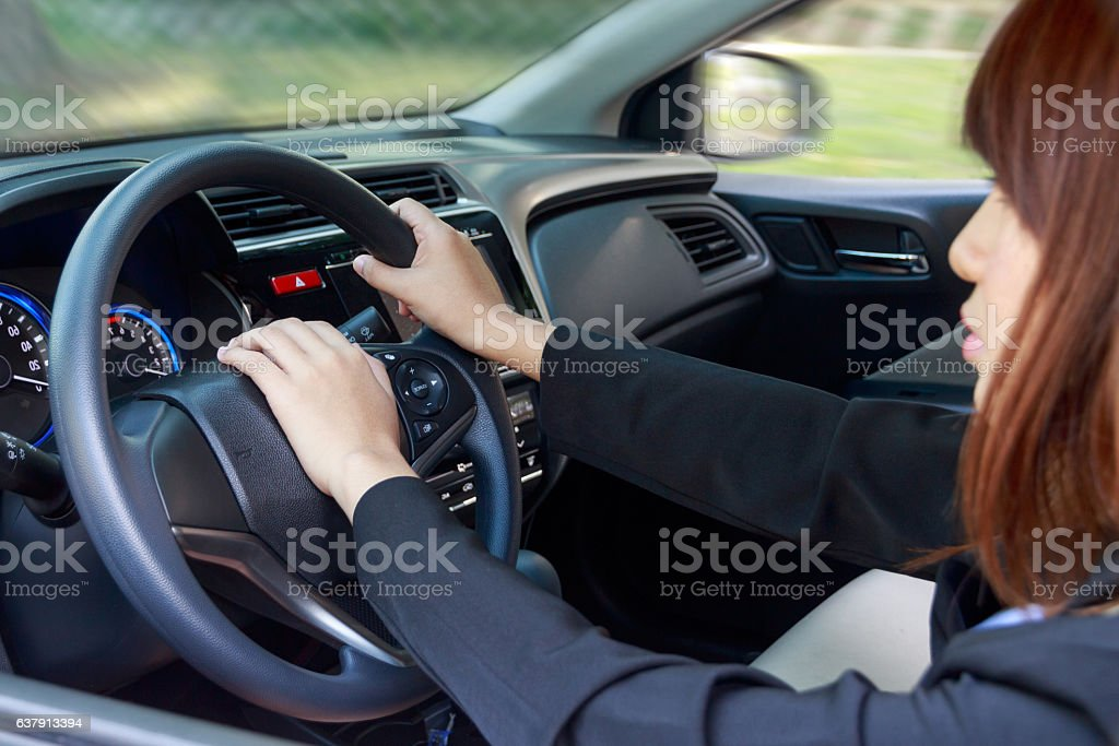 Woman driving a car and pressing on horn button stock photo