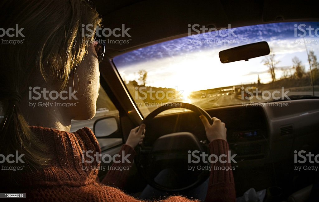 Woman Driving a Car At Sunset royalty-free stock photo