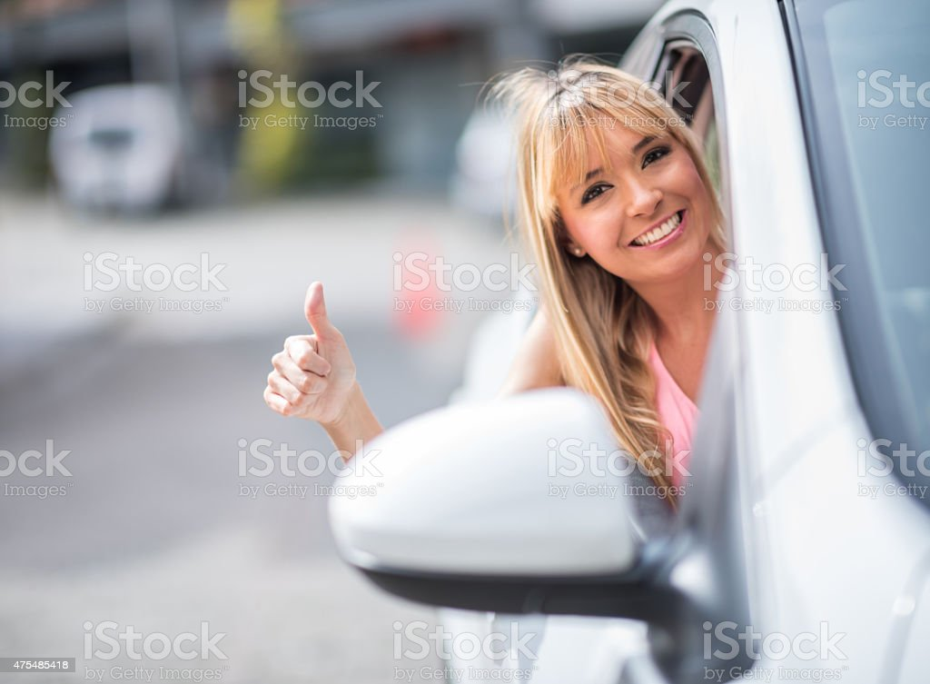 Woman driving a car with thumbs up stock photo