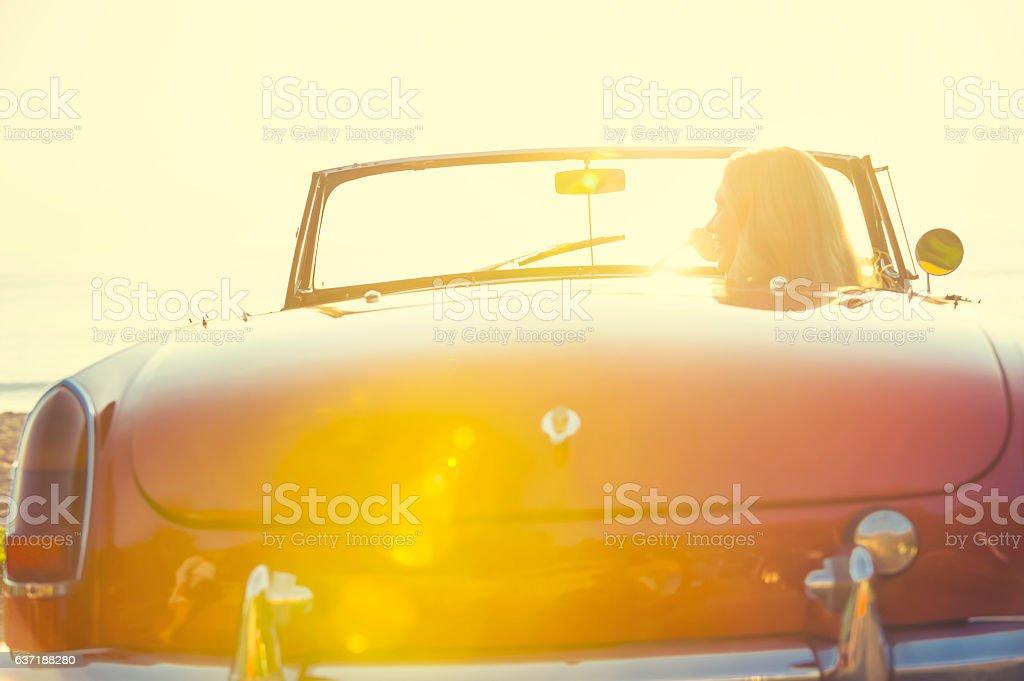 Woman driving a convertible car at the beach. stock photo