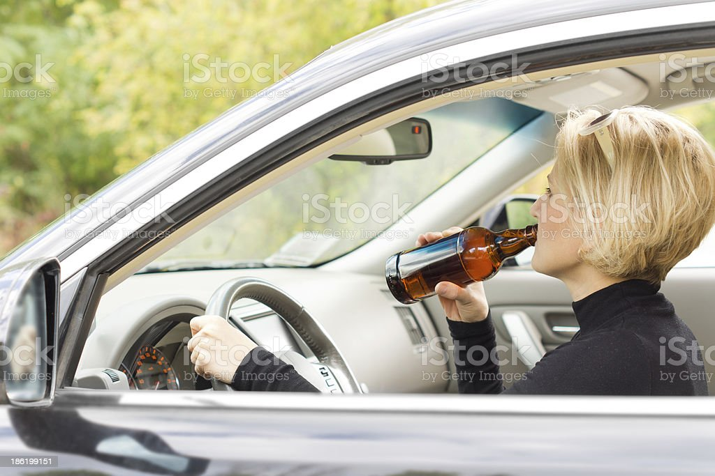 Woman driving along drinking alcohol royalty-free stock photo