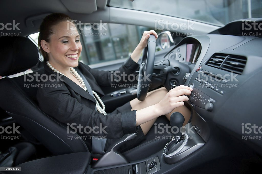 woman driving and changing radio station stock photo