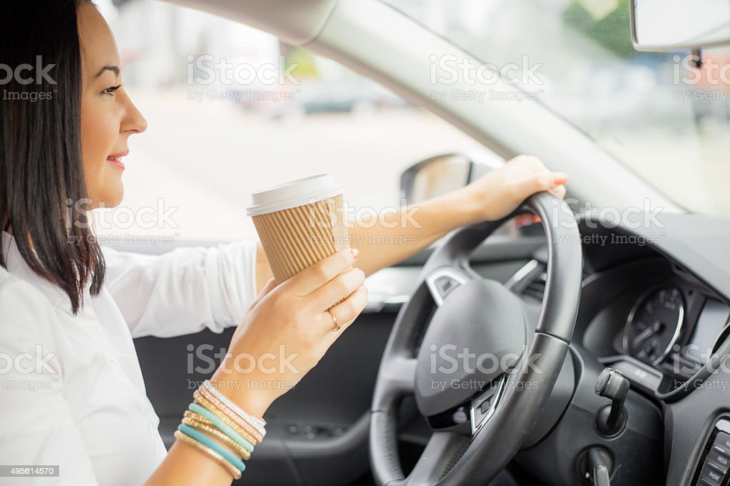 Woman driving and holding a coffee cup stock photo