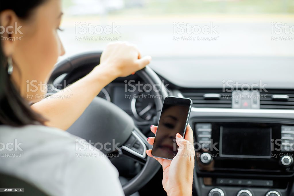 Woman driving and looking at cellphone stock photo