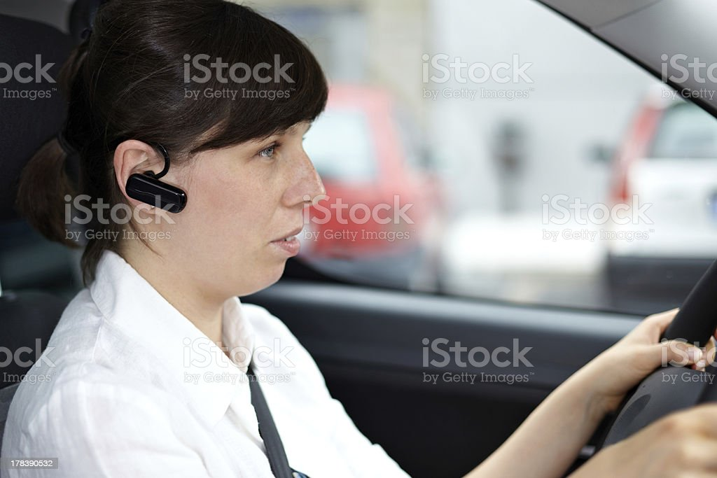 woman driving and talking phone in a car using headset royalty-free stock photo
