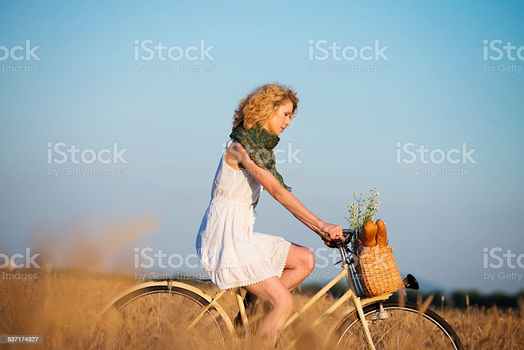 Woman driving bicycle through wheat field stock photo