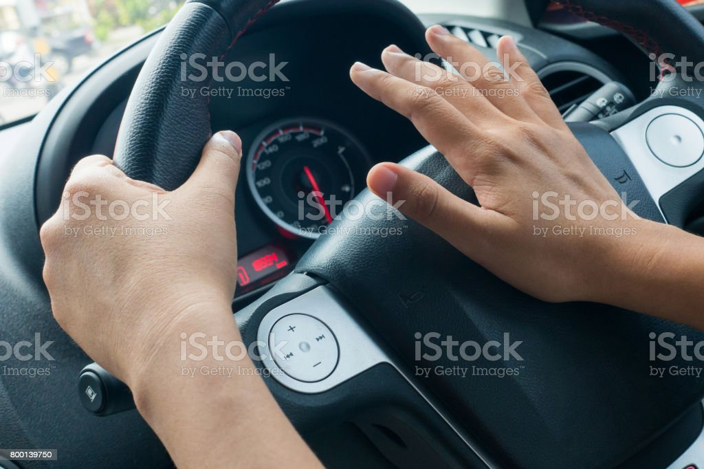 woman driving car and honking. stock photo