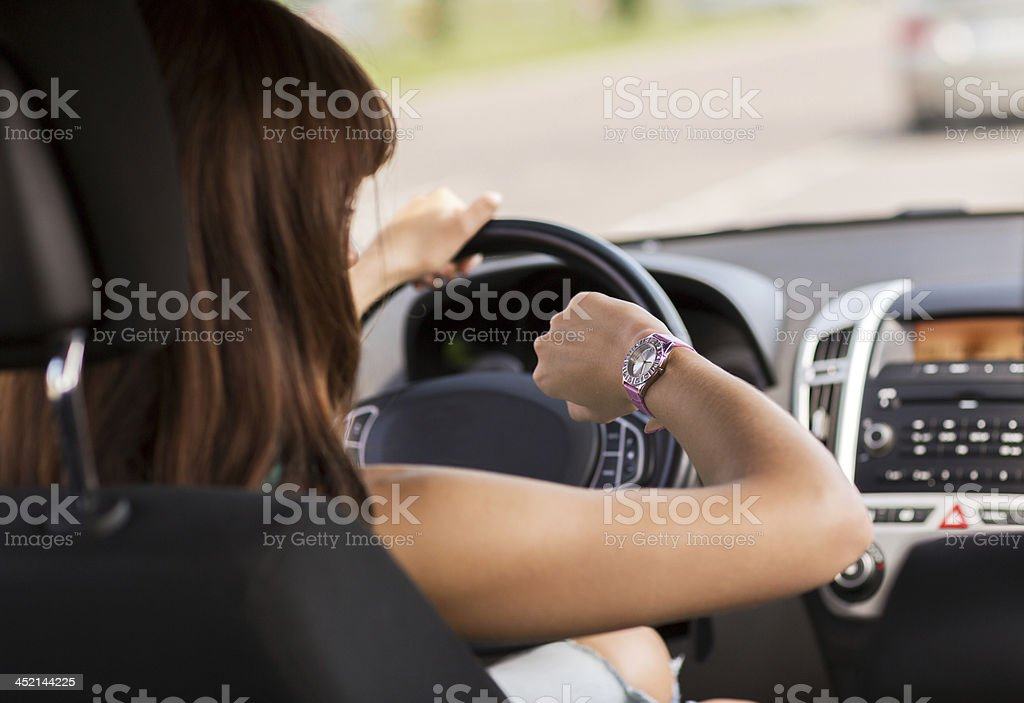 woman driving car and looking at watch stock photo