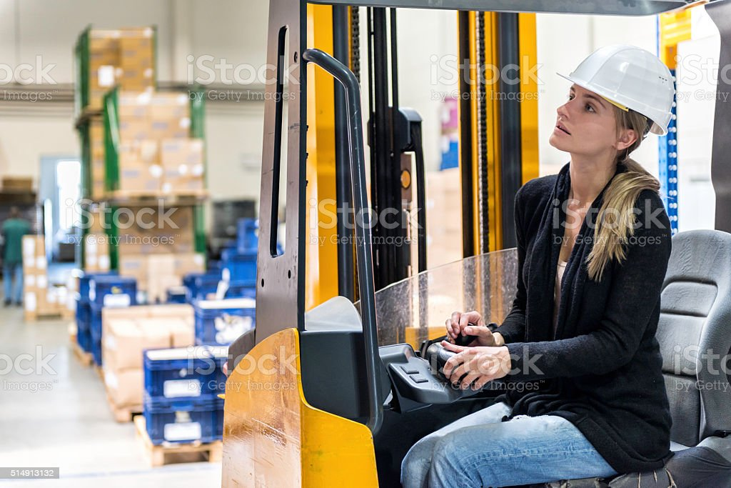 Woman driving forklift stock photo