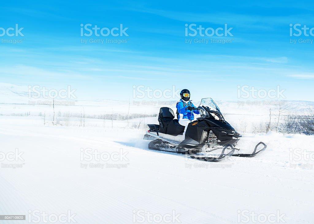 Woman driving snowmobile stock photo