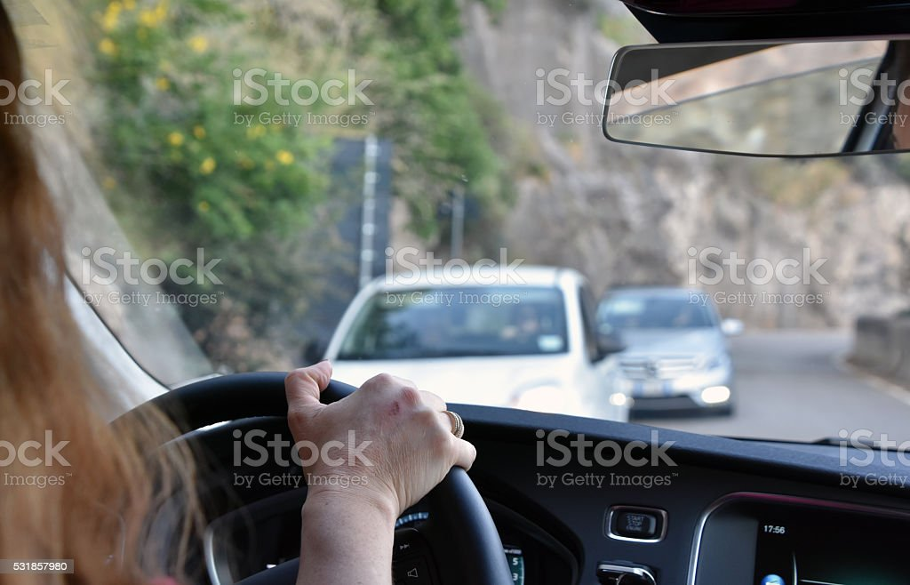 Woman driving through the narrow streets of Italy stock photo