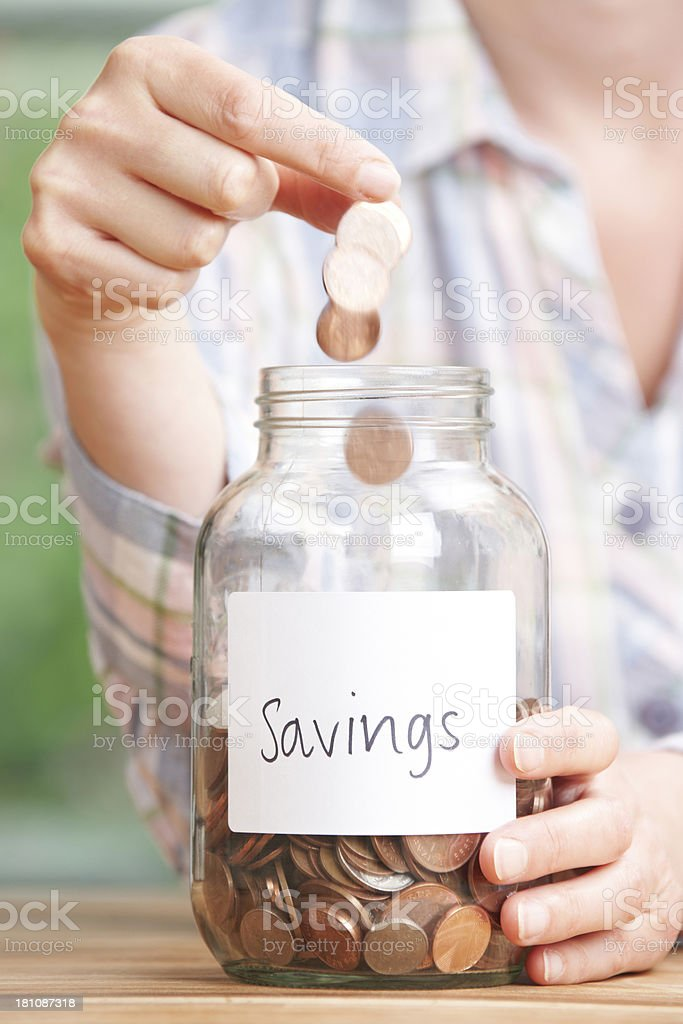 Woman Dropping Coins Into Jar Labelled Savings royalty-free stock photo