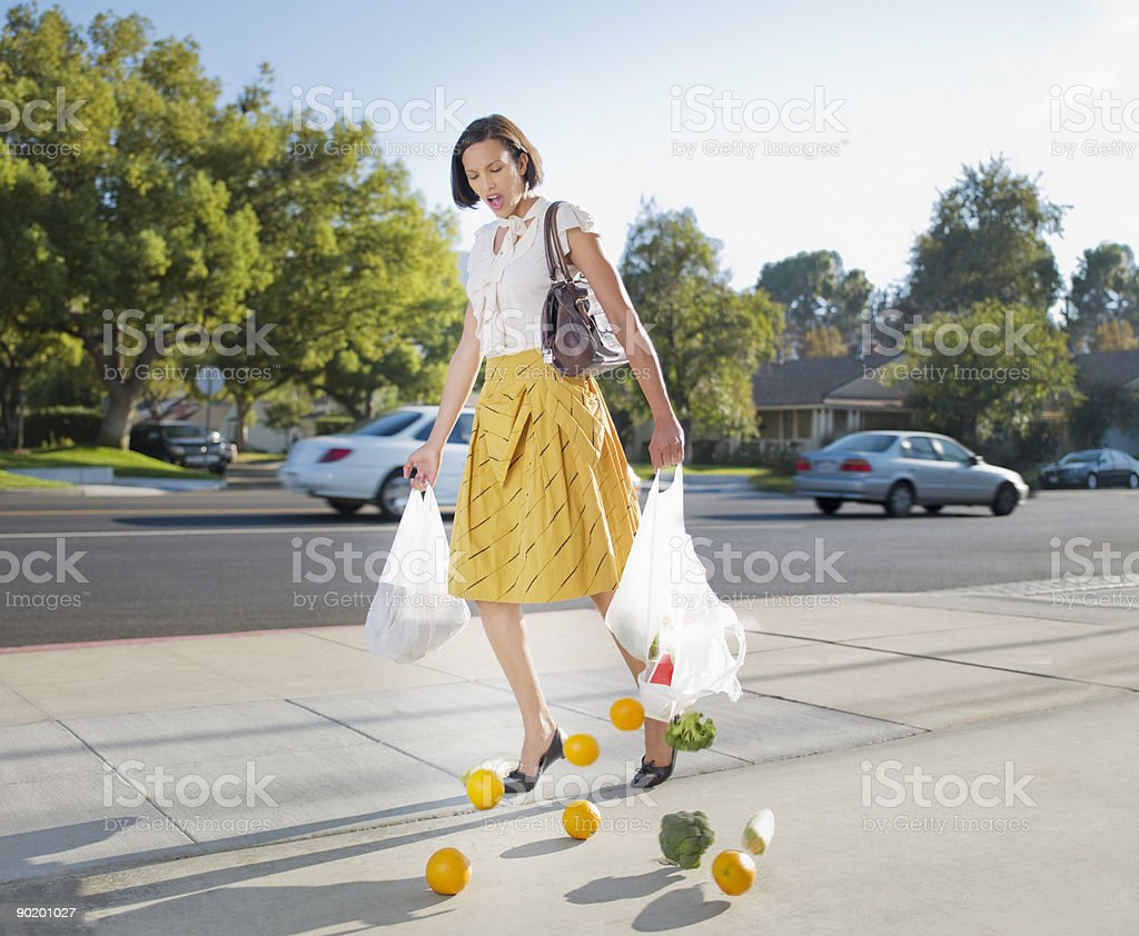 Woman dropping groceries on sidewalk stock photo
