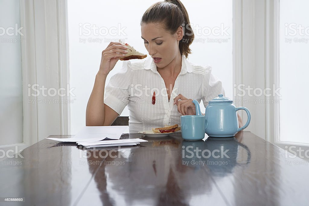 Woman dropping jam down her blouse at breakfast stock photo