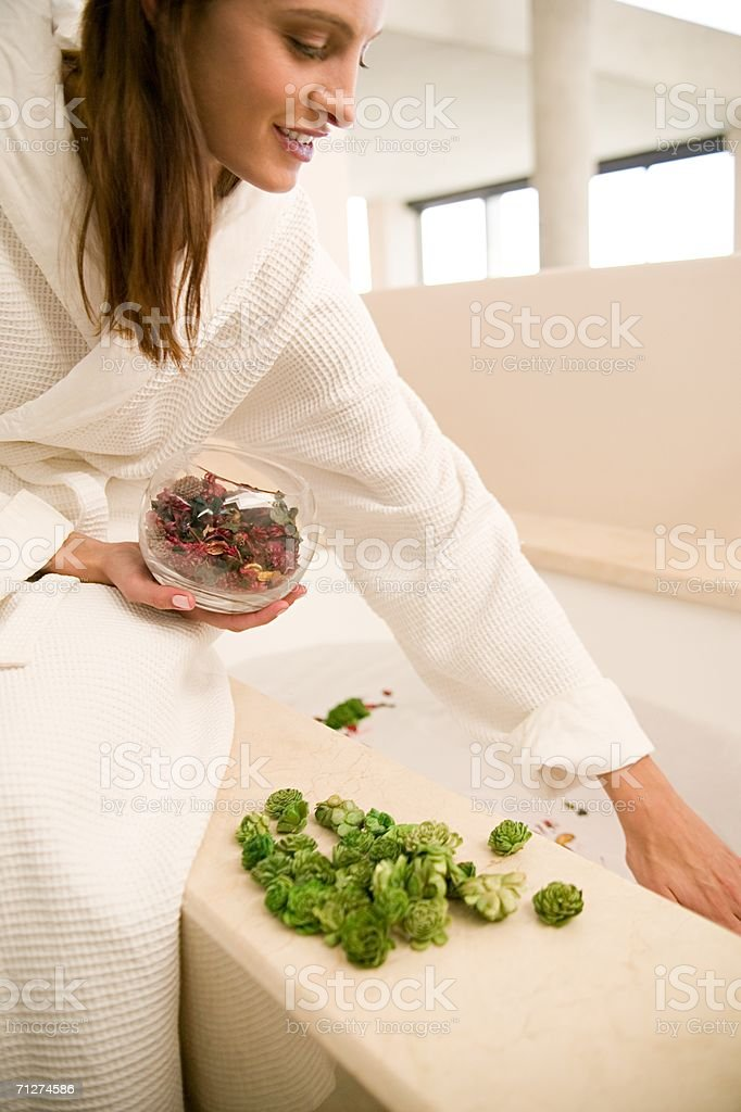 Woman dropping rose petals in bath stock photo