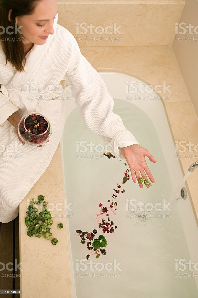 Woman dropping rose petals into bath stock photo