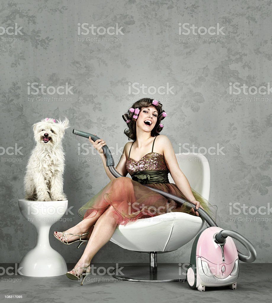 Woman drying dog fur with vacuum stock photo
