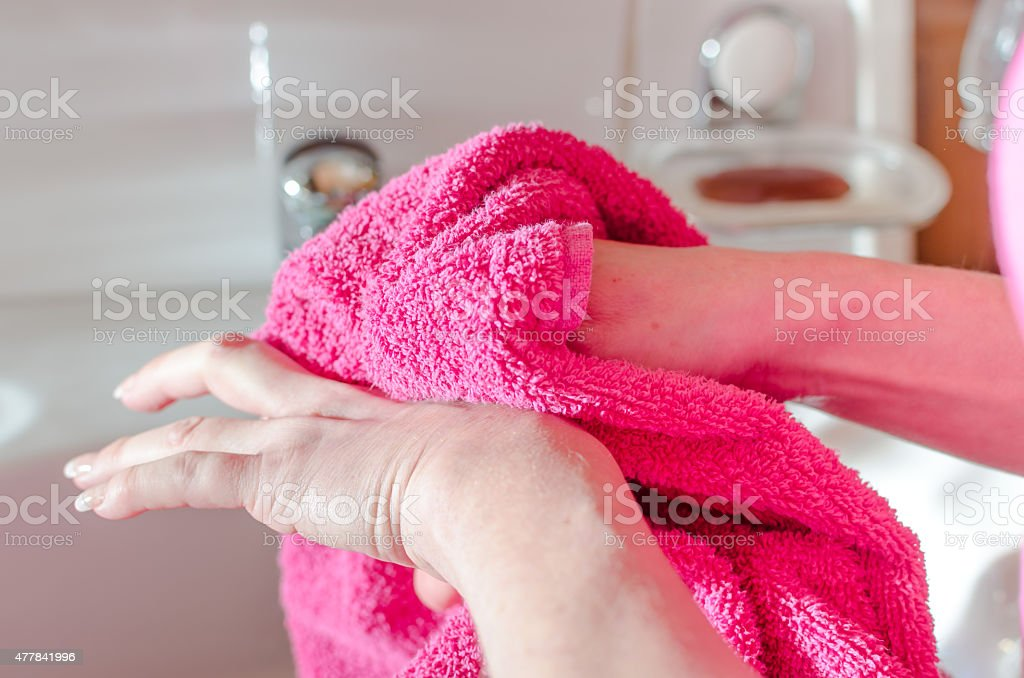 Woman drying her hands with a towel stock photo