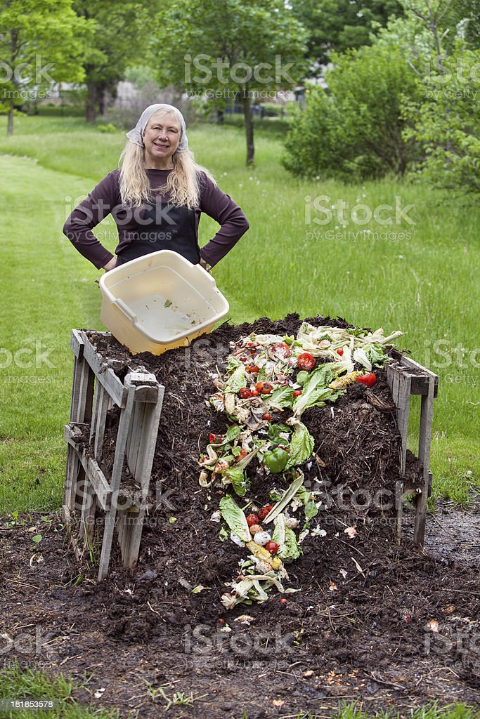 woman dumping scraps on top of compost pile ii royalty-free stock photo