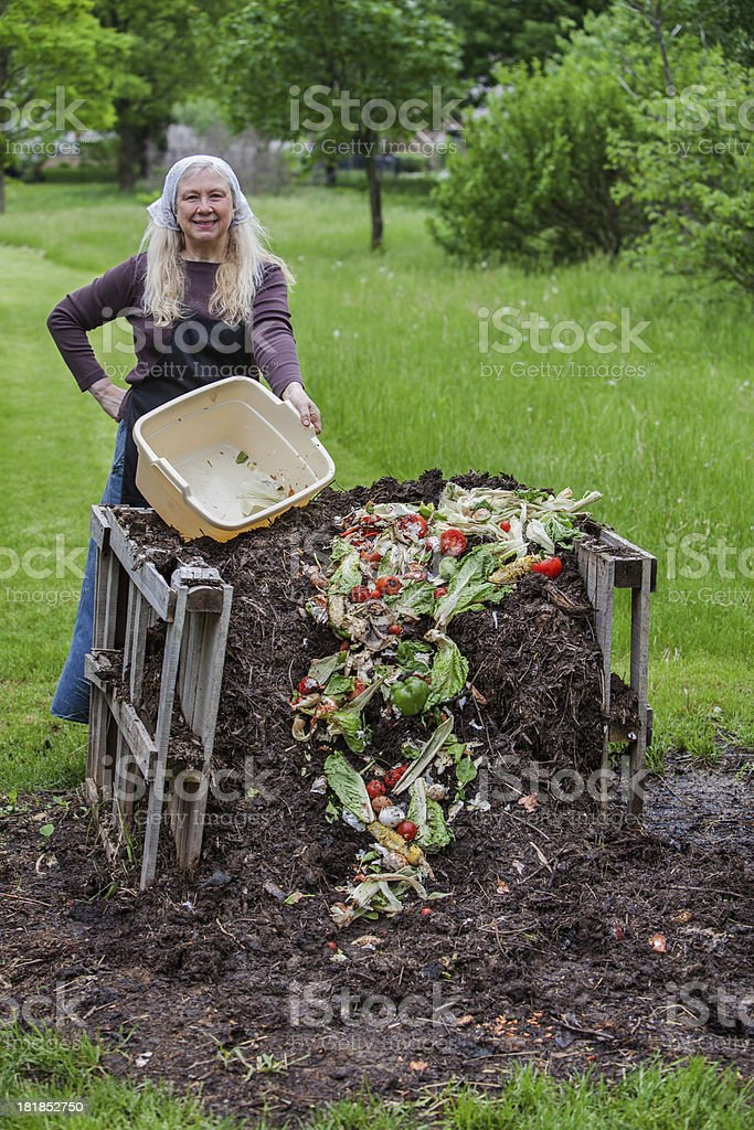 woman dumping scraps on top of compost pile royalty-free stock photo
