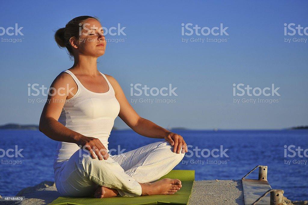 woman during yoga meditation on the beach stock photo
