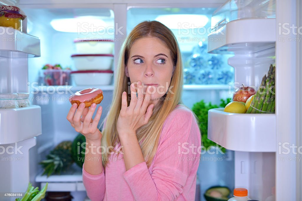 Woman eating a donut at night stock photo