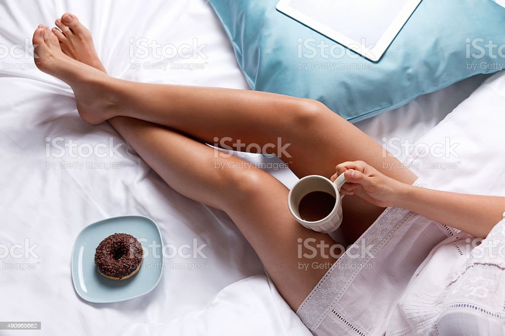 Woman eating a donut in the bed stock photo