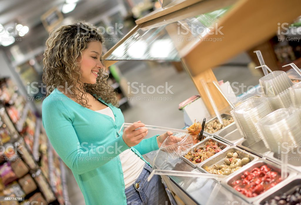 Woman eating a salad from a grocery store stock photo