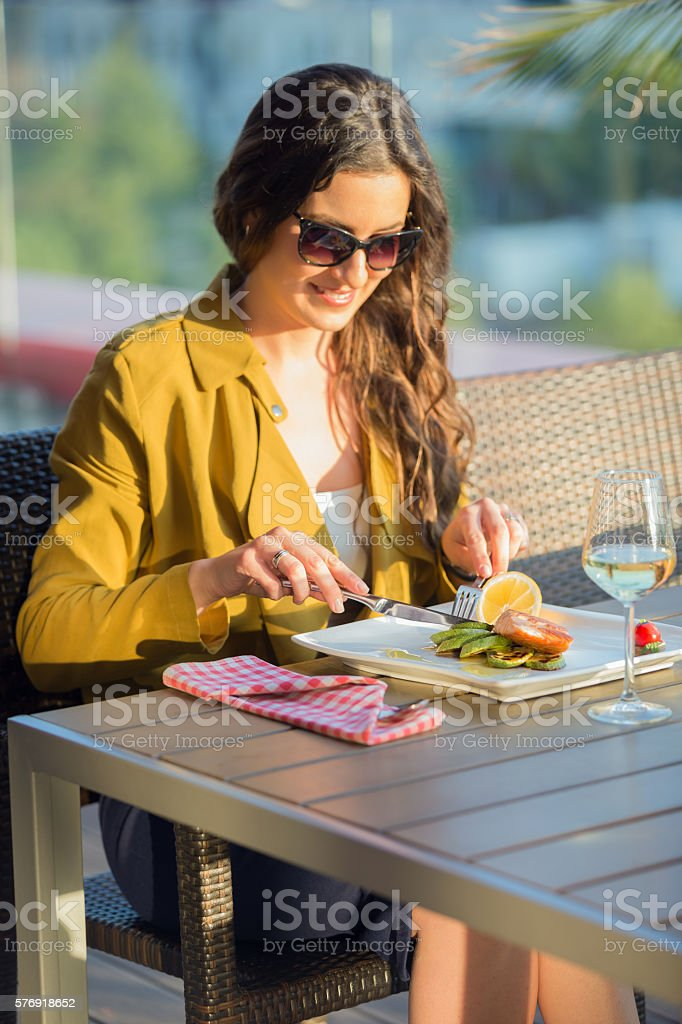 Woman eating at outdoor restaurant stock photo