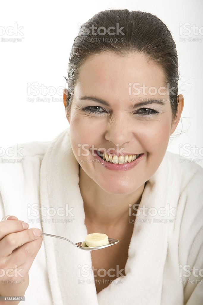 Woman eating banana from spoon stock photo