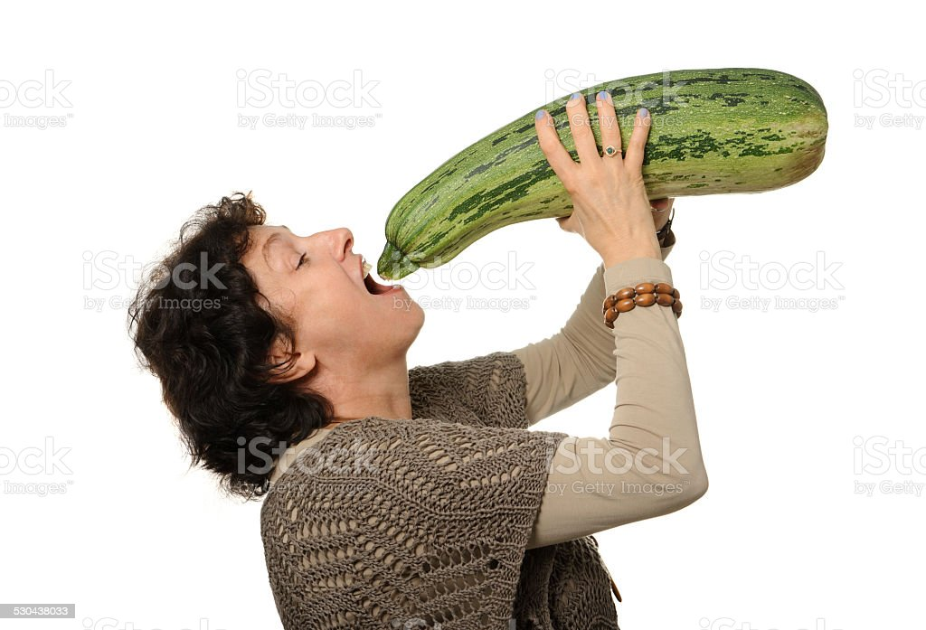 Woman eating big courgette (zucchini) stock photo