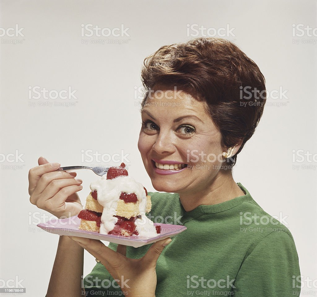Woman eating cake, smiling, portrait stock photo