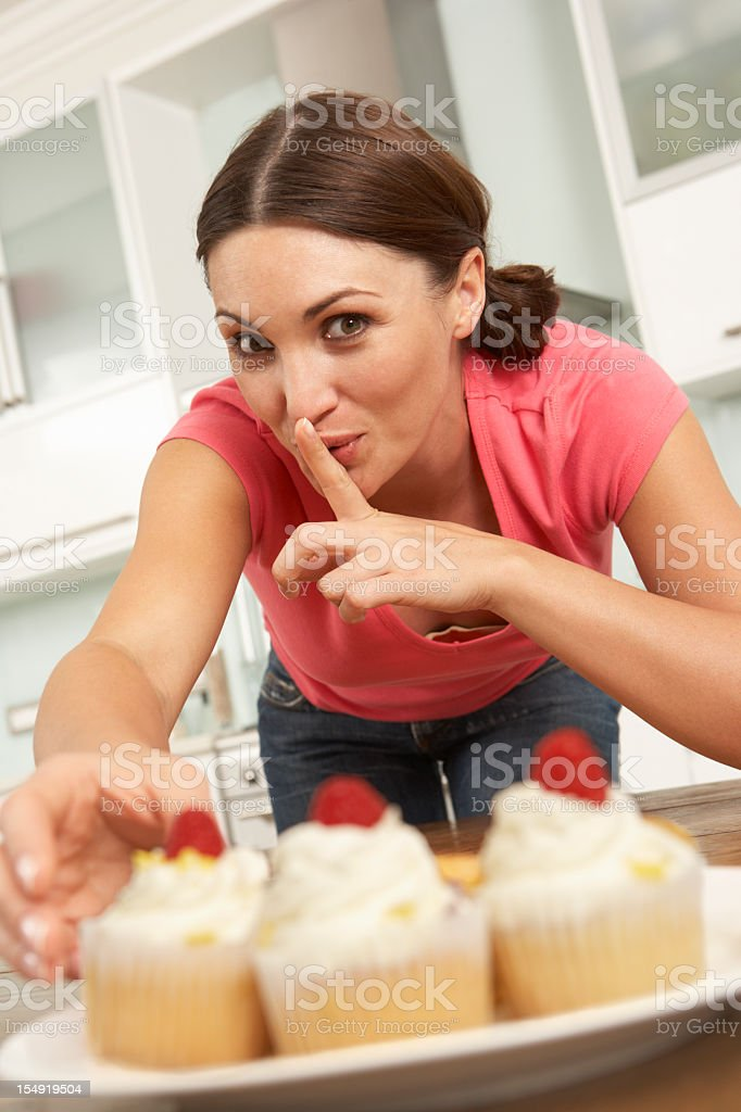 Woman Eating Cakes In Kitchen royalty-free stock photo